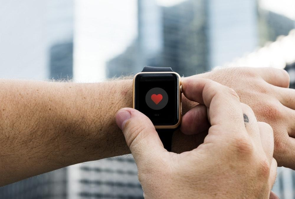 person holding Apple Watch during daytime