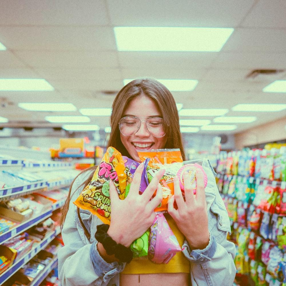 smiling woman holding pack of food inside grocery store